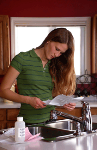 attractive girl taking water sample at kitchen sink to get water quality test done